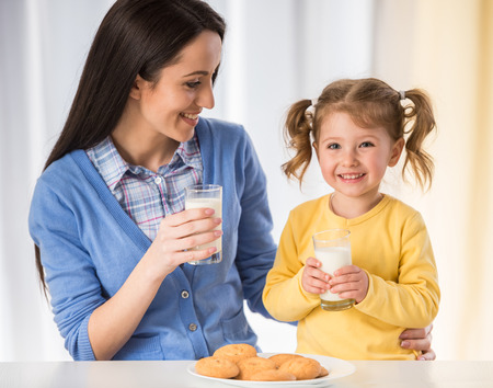 Photo pour Adorable girl is having an healthy snack with cookies and milk with her mother. - image libre de droit