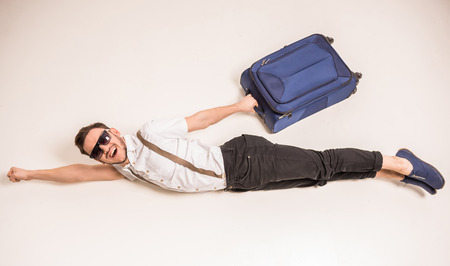 Foto de Young creative man is posing with suitcase on grey background. - Imagen libre de derechos