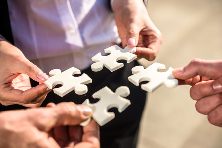 Closeup of business people wanting to put four pieces of puzzle together.