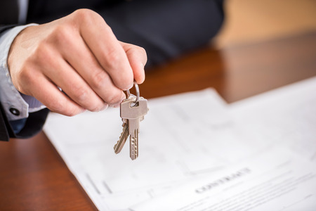 Photo pour Close-up of hand of man is holding a key from a new apartment. - image libre de droit