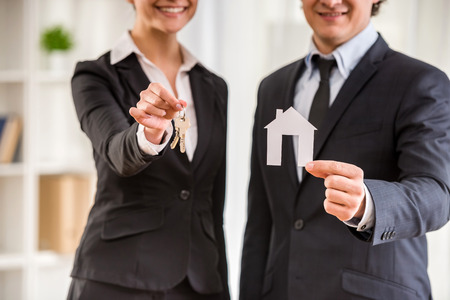 Two realtors in suits are showing a model of house and keys.