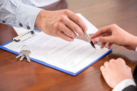 Photo pour Young woman is signing financial contract with male realtor. Close-up. - image libre de droit