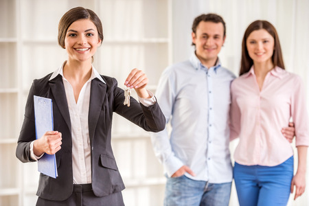 Photo pour Realtor woman is holding keys and young couple on background. - image libre de droit