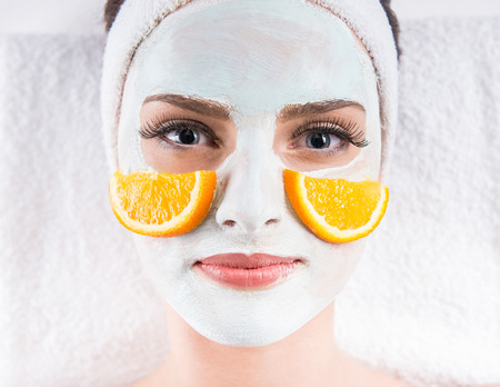Photo pour Young beautiful woman holding orange slices and mask on the face in a spa salon. - image libre de droit