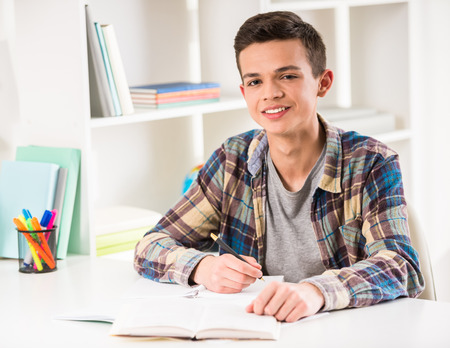 Young smiling boy sitting at the table and doing homework at home.