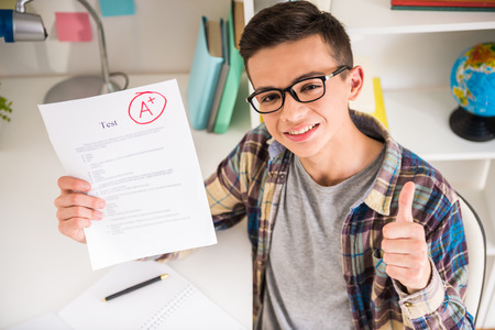 Portrait of teenager sitting at the table at home and showing perfect test results.