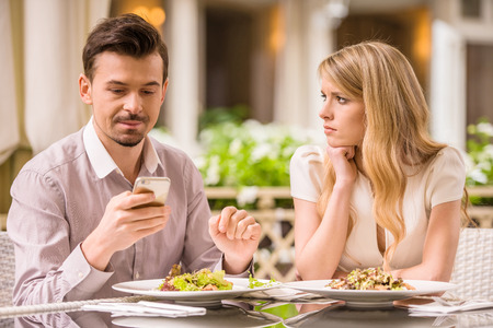 Young smiling couple in gorgeous restaurant. Man looking at phone.