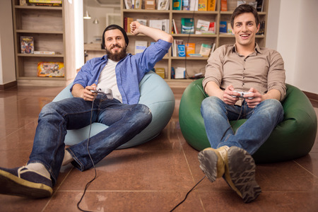 Two young handsome guys sitting on poufs and playing video games together. Leisure time.