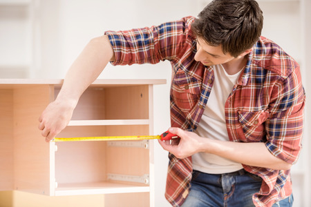 Young man measuring home furniture with measure tape. Repair concept.