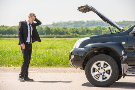 Photo pour Full length of businessman with hands on head standing by broken down car at countryside. - image libre de droit