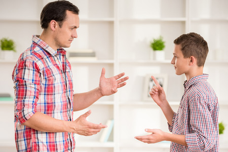 Father and son dressed casual having quarrel at home.