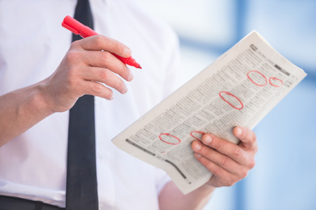Close-up of unemployed man in suit reading newpaper outdoors.