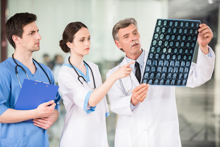 Photo pour Group of doctors looking at X-ray at offie. - image libre de droit