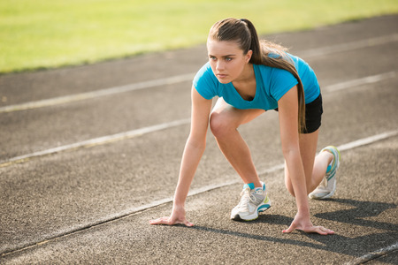 Attractive sporty girl ready to run sprint. Female athlete in powerful starting line pose.