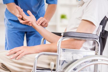 Male nurse taking pulse of senior patient at hospital.