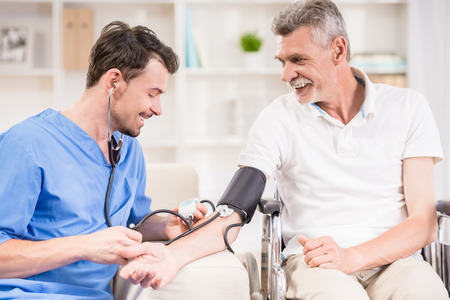 Male doctor measuring blood pressure to older patient sitting at wheelchair.