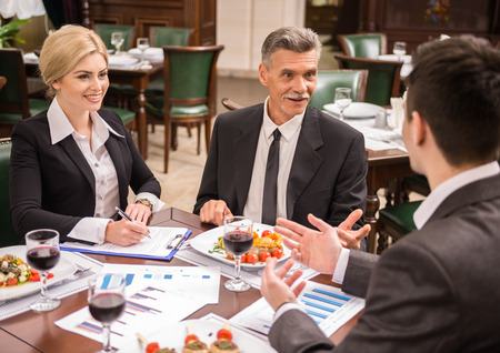Photo pour Group of successful business people discussing contract during business lunch. - image libre de droit