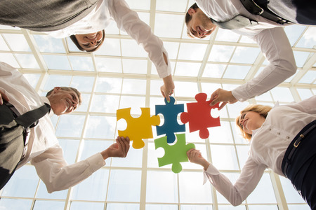 Group of business people assembling jigsaw puzzle and represent team support and help concept.の写真素材