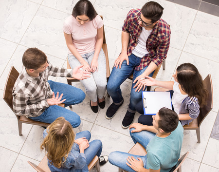 Group therapy. Group of people sitting close to each other and communicating.