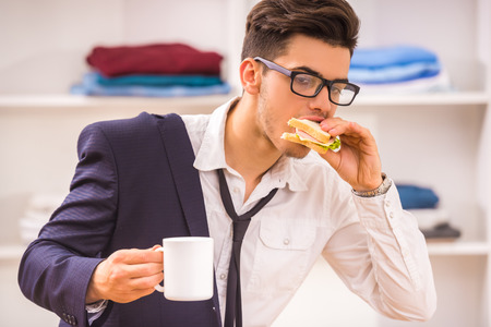 Photo pour Stylish man in glasses eating his breackfast while hurring to work. - image libre de droit