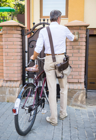 Rear view of senior man with bicycle is ringing an intercom of an apartment building.