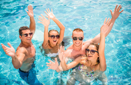 Beautiful young people having fun in swimming pool, smiling.