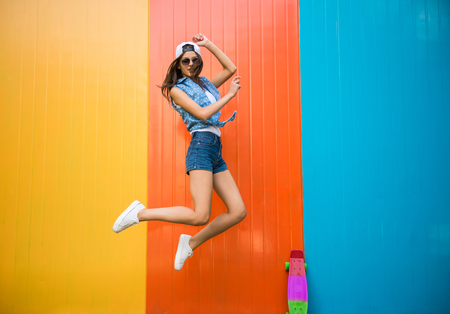 Foto de Pretty young woman is jumping with against the colorful wall. - Imagen libre de derechos