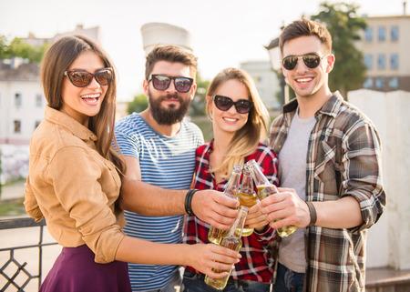 Photo pour Young happy people walking outdoors. Drinking beverages - image libre de droit
