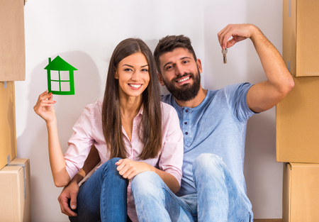 Photo pour Young happy couple holding keys of new home, moving to a new home concept - image libre de droit