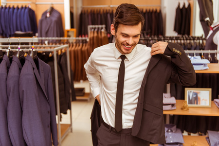 Foto de Modern young handsome businessman smiling and trying on classical suit in the suit shop - Imagen libre de derechos
