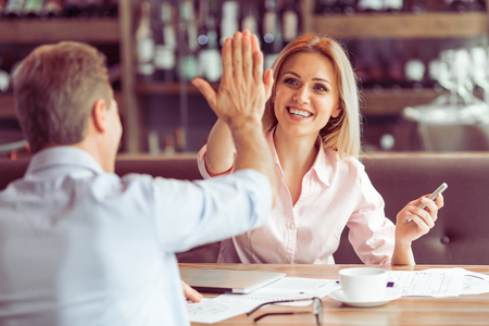 Photo pour Beautiful business woman is giving high five and smiling to man during business meeting at the restaurant - image libre de droit