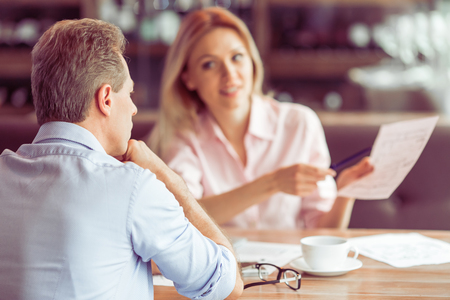 Beautiful business woman is holding a document and explaining business affair to man during business meeting at the restaurant