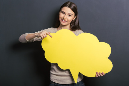 Photo pour Beautiful young female student is holding a yellow speech bubble, pointing on it and smiling, standing against blackboard - image libre de droit