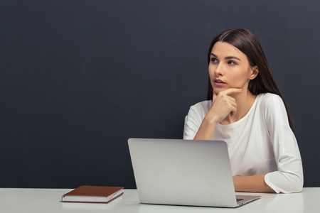 Photo pour Thoughtful beautiful student in white blouse is keeping hand on chin and thinking, sitting at a table with a laptop against blackboard - image libre de droit