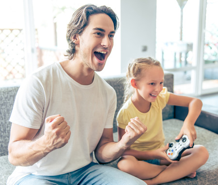 Photo pour Handsome father and his cute little daughter are playing game console and smiling while sitting on couch at home. Dad is cheering for his child - image libre de droit
