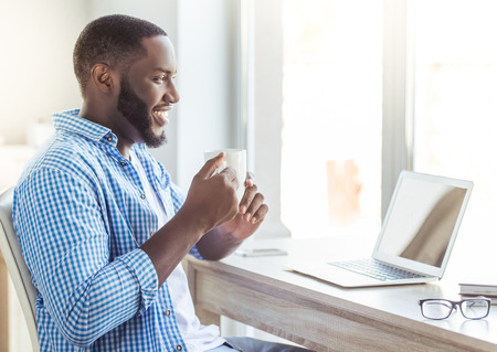 Foto de Side view of handsome Afro American man in casual clothes holding a cup and smiling while sitting at table at home - Imagen libre de derechos