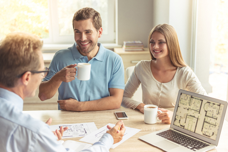 Photo pour Handsome middle aged realtor in classic shirt and eyeglasses and happy young couple are discussing new house. Couple is drinking coffee and smiling while sitting in office - image libre de droit