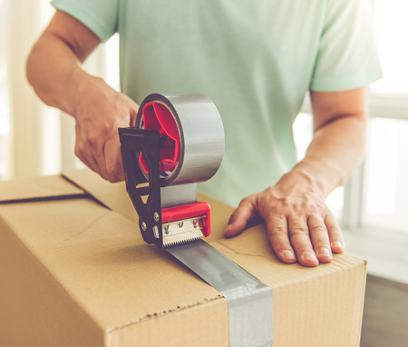 Photo pour Cropped image of handsome mature man in casual clothes packing his stuff into the boxes using an adhesive tape while moving to the new apartment - image libre de droit