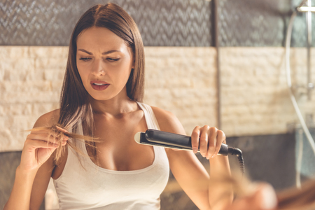 Photo pour Beautiful young woman in white undershirt is looking at her damaged hair while using a hair straightener, standing in front of the mirror in the bathroom - image libre de droit