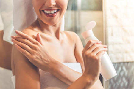 Photo pour Cropped image of beautiful young woman in bath towel applying body lotion on her shoulders and smiling while standing in bathroom - image libre de droit