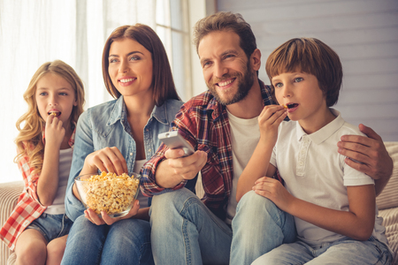 Photo pour Beautiful young parents and their children are watching TV, eating popcorn and smiling while sitting on couch at home - image libre de droit