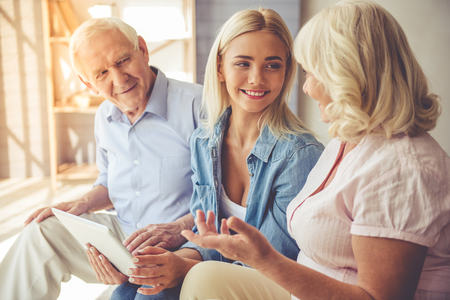Foto de Beautiful old couple and young girl are using a digital tablet, talking and smiling while sitting on couch at home - Imagen libre de derechos