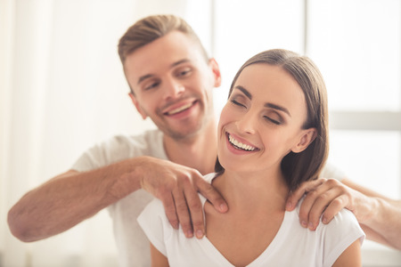 Photo pour Handsome young man is doing his beautiful girlfriend massage and smiling while they are resting at home - image libre de droit