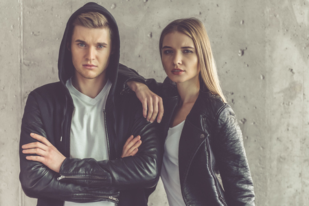 Beautiful stylish couple in leather jackets is looking at camera while standing on concrete wall background