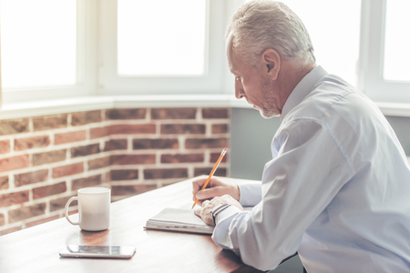 Photo pour Handsome mature businessman in formal suit is writing in his notebook while working in office - image libre de droit
