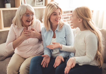 Photo pour Three generations of women. Beautiful granny, mother and daughter are hugging, talking and smiling while sitting on couch at home - image libre de droit