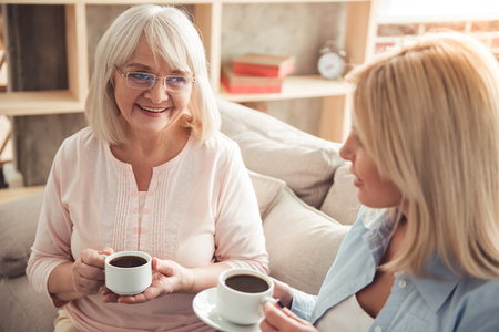 Foto de Beautiful mature mother and her adult daughter are drinking coffee, talking and smiling while sitting on couch at home - Imagen libre de derechos