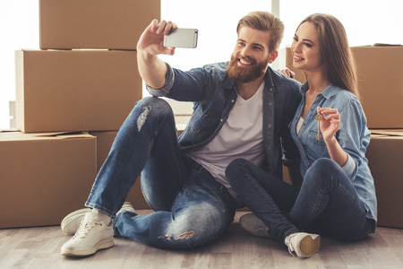 Beautiful young couple is doing selfie using a smart phone and smiling while sitting among moving cardboard boxes