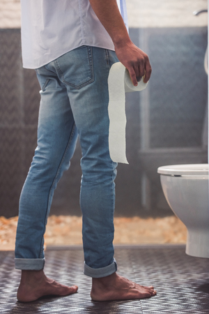 Cropped image of handsome Afro American man in jeans holding a toilet paper while standing near the toilet