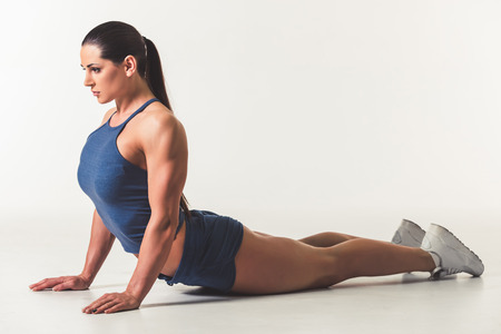 Beautiful strong woman in sportswear is stretching, on light background